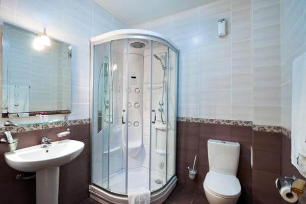 Кабина из стекла, сделанная уголком, устанавливается на пол или на небольшом возвышении.