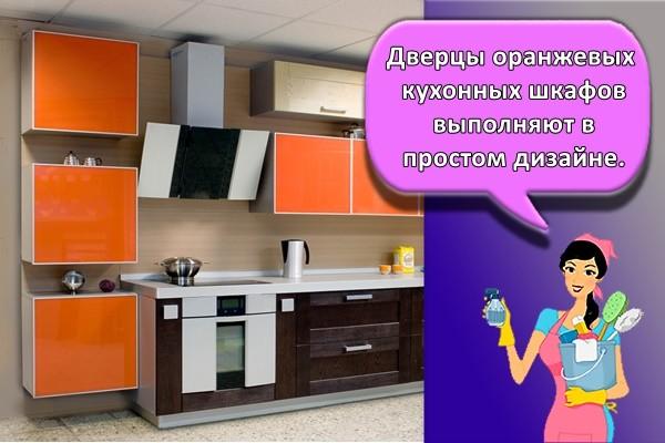 Дверцы оранжевых кухонных шкафов выполняют в простом дизайне.